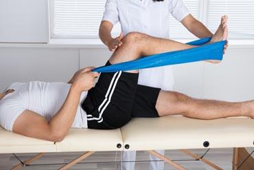 Mann wird mit Krankengymnastik behandelt